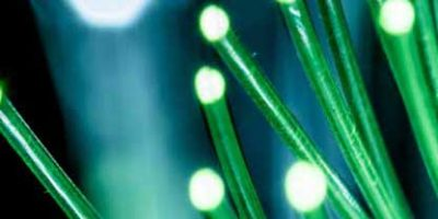 Bundle of optical fibers with green light. Black background.